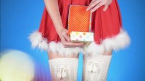 lycklig flicka med loppfallet ung attraktiv kvinna i en jungfru- dräkt för snö med en gåva som dansar på en blå bakgrund Närbild stock video