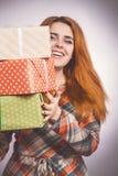 Lycklig flicka med massor av gåvor i händer, en ung kvinna som rymmer en bunt av askar som slås in i dekorativt papper, begreppsf royaltyfri foto