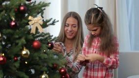 Lycklig flicka med modern som dekorerar julgranen lager videofilmer