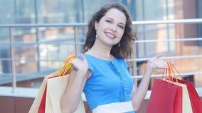 Lycklig flicka med packar, når att ha shoppat lager videofilmer