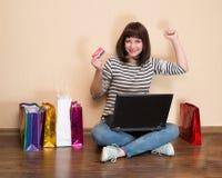 Lycklig flicka med shoppingpåsar som sitter på golvet med bärbar dator a Royaltyfri Bild