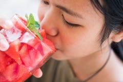 Lycklig flicka när dricksvattenmelonfruktsaft royaltyfria bilder