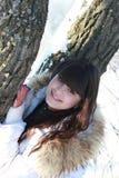 Lycklig flicka nära ett träd i en vinterskog Fotografering för Bildbyråer