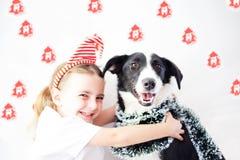 Lycklig flicka och hund på jul Fotografering för Bildbyråer