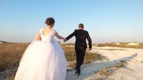 Lycklig flicka- och mankörning på vägen som rymmer händer Koppla ihop förälskat på en bröllopsresatur Ett gift par p? semester stock video