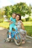 Lycklig flicka på en cykel med hennes moder Royaltyfri Foto