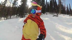 Lycklig flicka på en snowboard som glider ner lutningen arkivfilmer
