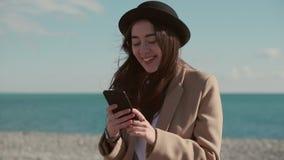 Lycklig flicka på en strand med en telefon lager videofilmer