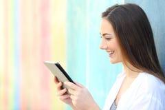 Lycklig flicka på hållande ögonen på massmedia för en färgrik vägg på minnestavlan royaltyfri bild