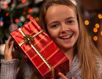Lycklig flicka på jultid med en gåva fotografering för bildbyråer
