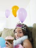 Lycklig flicka på soffan med ballonger och muffin Arkivbilder