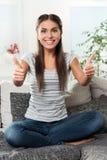 Lycklig flicka på soffan som pekar upp hennes tummar Royaltyfri Fotografi