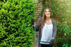 Lycklig flicka som är utomhus- i trädgården som arbeta i trädgården som hobby royaltyfri fotografi