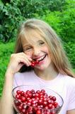 Lycklig flicka som äter Cherryet fotografering för bildbyråer