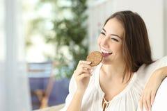 Lycklig flicka som äter en dietisk kaka royaltyfri bild