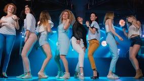 Lycklig flicka som åtta flörtar och dansar på danceflooren, i en nattklubb lager videofilmer