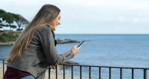 Lycklig flicka som använder en smart telefon i en balkong