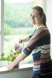 Lycklig flicka som besprutar en växt i kruka Fotografering för Bildbyråer