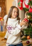 Lycklig flicka som dekorerar julgranen på vardagsrum Royaltyfria Bilder
