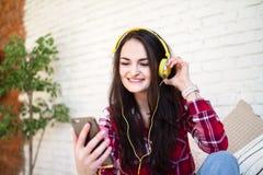 Lycklig flicka som direktanslutet lyssnar till musik från ditt smartphonesammanträde på soffan hemma fotografering för bildbyråer