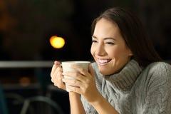 Lycklig flicka som dricker coffe i natten fotografering för bildbyråer