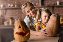 Lycklig flicka som förbereder en pumpa för allhelgonaafton med hennes moder Arkivfoto