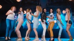 Lycklig flicka som flörtar och dansar på danceflooren, i en nattklubb lager videofilmer