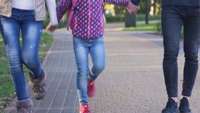 Lycklig flicka som går med föräldrar efter skola, skryta av att intressera grupper arkivfilmer