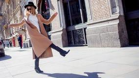 Lycklig flicka som g?r ner gatan, solig dag Trendigt och moderiktigt royaltyfri bild