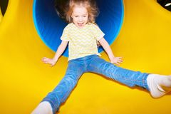 Lycklig flicka som går ner glidbana royaltyfri foto