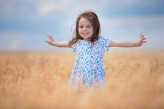Lycklig flicka som g?r i guld- vete som tycker om livet i f?ltet Natursk?nhet, bl? himmel och vete?ker utomhus- familj arkivfoto