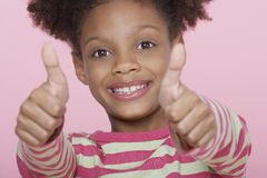 Lycklig flicka som ger upp dubbla tummar Arkivfoto