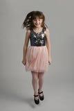 Lycklig flicka som ha på sig elegant klänningbanhoppning Royaltyfria Foton