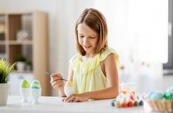 Lycklig flicka som hemma färgar easter ägg royaltyfria bilder