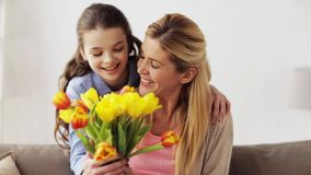 Lycklig flicka som hemma ger blommor till modern lager videofilmer