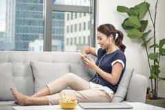 Lycklig flicka som hemma lyssnar till musik från mobiltelefonsammanträde på en soffa arkivfoton