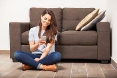 Lycklig flicka som hemma smsar på en smartphone Arkivfoton