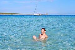 Lycklig flicka som kopplar av i det kristallklara havet, La Pelosa, Sardinia, Italien Arkivfoton