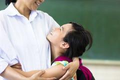 Lycklig flicka som kramar hennes moder i klassrum Arkivfoto