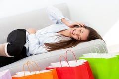 Lycklig flicka som lägger på soffan med den mobila telefonen Royaltyfri Bild