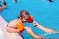 Lycklig flicka som l?r att simma i simbass?ng royaltyfri foto