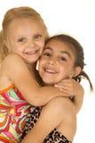 Lycklig flicka som lyfter hennes lilla syster som bär upp baddräkter Arkivfoton