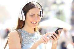 Lycklig flicka som lyssnar till musik som bläddrar den smarta telefonen arkivfoto