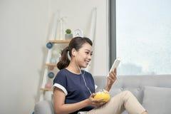 Lycklig flicka som lyssnar till musik från mobiltelefonsammanträde på en cou royaltyfria bilder