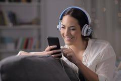 Lycklig flicka som lyssnar till musik som kontrollerar telefonen i natten royaltyfri foto