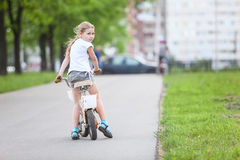 Lycklig flicka som rider en cykel, copyspace Arkivbild