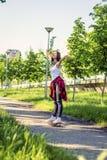 Lycklig flicka som rider skateboarder p? gatan royaltyfri foto