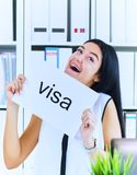 Lycklig flicka som rymmer en affisch med inskriftvisumet Unga flickan mottog ett arbetsvisum i Förenta staterna flicka royaltyfria foton
