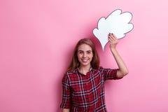 Lycklig flicka som rymmer en pappers- bild av den över huvudet tanke eller idén och glatt skrattar Royaltyfri Bild