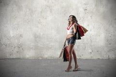 Lycklig flicka som rymmer många shoppingpåsar Royaltyfri Bild